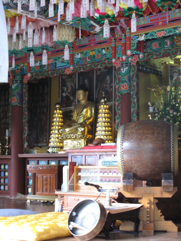 A golden Buddha statue inside the temple building.